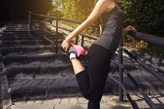 Young woman runner stretching legs Stock Photos