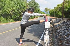 Young woman runner stretching legs before running outdoor. In the forest mountain road Royalty Free Stock Photography