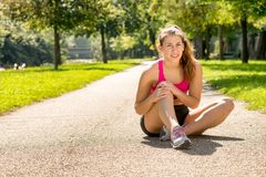 Young woman runner touching knee in pain outdoors stock images
