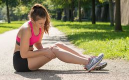 Young woman runner touching knee in pain outdoors. A young woman runner touching knee in pain outdoors stock images
