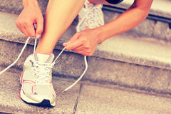 Young woman runner tying shoelace Stock Photos