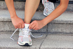 Young woman runner tying shoelace Stock Photography