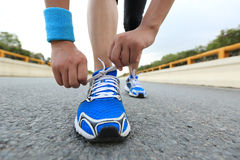 Young woman runner tying shoelaces Royalty Free Stock Photo