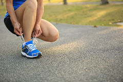 Young woman runner tying shoelaces Stock Photography
