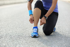 Young woman runner tying shoelaces. On city road Royalty Free Stock Photography