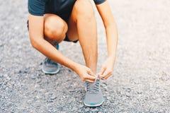 Young woman runner tying shoelaces Estilo de vida do esporte Imagem de Stock Royalty Free