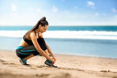 Young woman runner tying shoelaces Royalty Free Stock Images