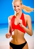 Young woman running. Young attractive happy smiling blond woman in sport wear running on sea beach Stock Photography