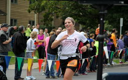 Young woman running across the finish line,Saratoga Springs,New york,September,2013. Young woman smiling victory as she runs across finish line at half marathon Royalty Free Stock Photo
