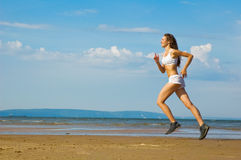 Young woman running alone on the beach Stock Photography