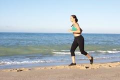 Young Woman Running Along Beach Stock Photos