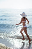 Young woman running along the beach. Stock Image