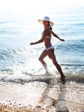 Young woman running along the beach. Royalty Free Stock Image