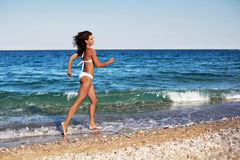 Young woman running along the beach. Royalty Free Stock Images