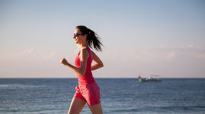 Young woman running along the coast Royalty Free Stock Photography