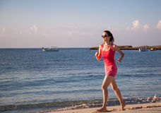 Young woman running along the coast Stock Images