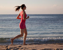 Young woman running along the coast Royalty Free Stock Image