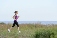 Young woman running along lake shore Stock Photos