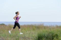 Young woman running along lake shore Stock Photos