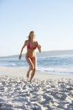 Young Woman Running Along Sandy Beach On Holiday Wearing Bikini Stock Photography
