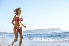 Young Woman Running Along Sandy Beach On Holiday Wearing Bikini Stock Photo