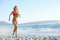 Young Woman Running Along Sandy Beach On Holiday Wearing Bikini Stock Image