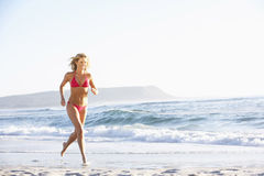 Young Woman Running Along Sandy Beach On Holiday Wearing Bikini Royalty Free Stock Image