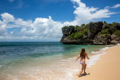 Young woman running along shore of ocean Stock Images