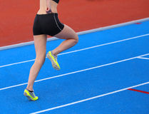 Young woman running on the athletics track with blue colored lan. Young woman running on the athletics track Stock Photography