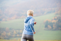 Young woman running in autumn nature, rear view Royalty Free Stock Photos