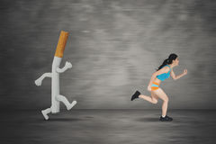 Young woman running away by a cigarette Royalty Free Stock Image