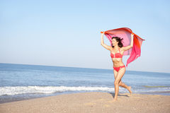 Young woman running on beach. Smiling royalty free stock photography