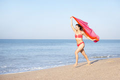 Young woman running on beach. Smiling stock image