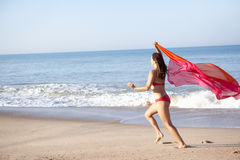 Young woman running on beach. In the sun stock photography