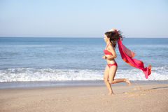Young woman running on beach. In the sun royalty free stock photos