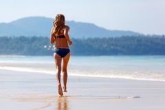 Young woman running on the beach Stock Image