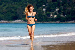 Young woman running on the beach Stock Photo