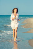 Young woman running on the beach Royalty Free Stock Photos
