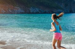 Young woman running on the beach stock photos