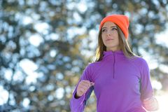 Young Woman Running in Beautiful Winter Forest at Sunny Frosty Day. Active Lifestyle Concept. Stock Photography