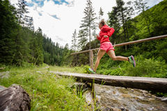 Young woman running on bridge in mountains on summer day Stock Photos