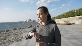 Young woman running and checking her cardio training data on her sport watch. Female jogger using heart rate monitor with running watch at seafront of the city stock footage