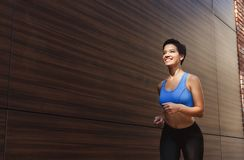 Young woman running in city copy space. Young brunette woman running in city near wooden wall, copy space Stock Images