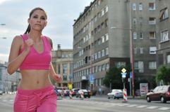 Young woman running in city road. Young woman running and training in city streets - cars and building (traffic background Royalty Free Stock Image