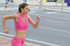 Young woman running in city road Stock Image