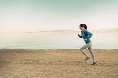 Young woman running on coastline Stock Photography