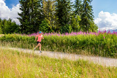 Young woman running on country road in mountains, summer day Stock Photo
