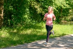 Young woman running in countryside. Blond young woman running on road in green countryside, summer scene Stock Photo
