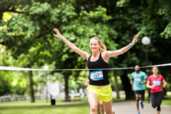 Young woman running in the crowd crossing the finish line. Royalty Free Stock Images