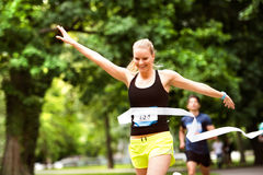 Young woman running in the crowd crossing the finish line. Stock Photography